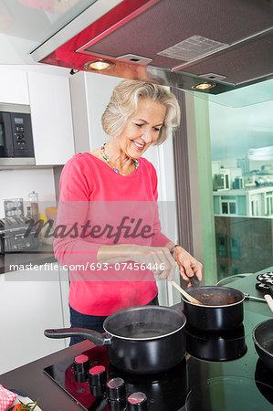 Smiling senior woman preparing food at kitchen counter