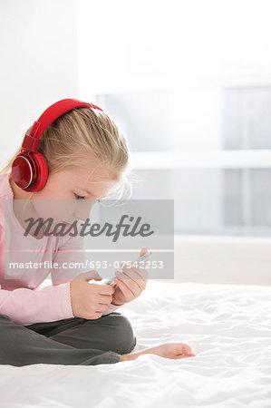 Cute girl listening music on smart phone in bedroom