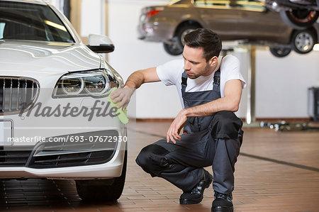 Full length of maintenance engineer cleaning car in workshop