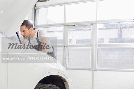 Young male maintenance engineer repairing car engine in workshop