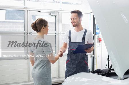 Smiling maintenance engineer shaking hands with female customer in car repair shop