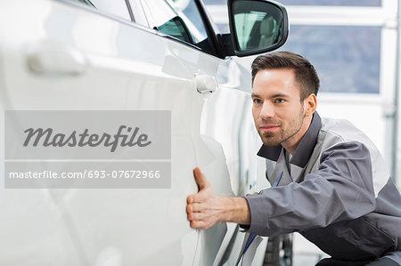 Young maintenance engineer examining car in repair shop