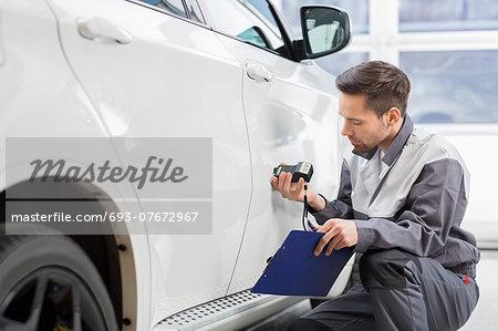 Male repair worker examining car paint with equipment in repair shop