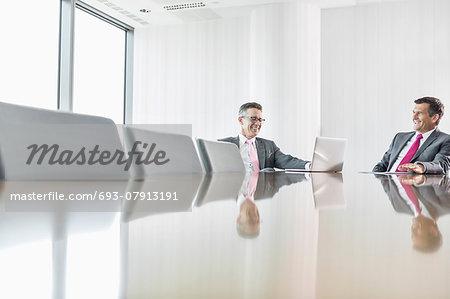 Smiling businessmen talking in conference room