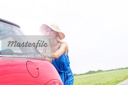 Woman pushing broken down car against clear sky