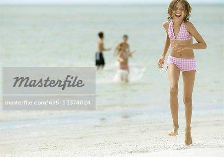 Girl running across beach