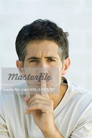Man, putting finger over lips, portrait