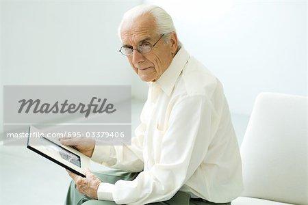 Senior man sitting, holding photograph, looking at camera
