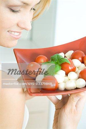 Woman holding up tomato mozzarella salad, smiling, cropped view