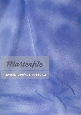 Folds in mottled lavender fabric, close-up, full frame