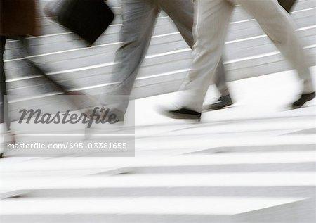 Business people walking on pedestrian crossings, low section, blurred