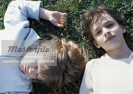 Girl and boy lying on grass