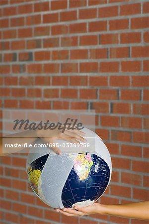 Hands holding a bandaged globe