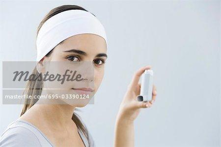 Teen girl holding inhaler, looking at camera