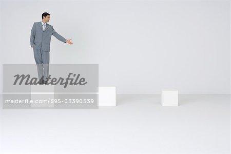 Businessman standing on pedestal, presenting empty pedestals