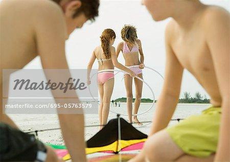 Boys preparing kite on beach, girls with hoola hoops in background