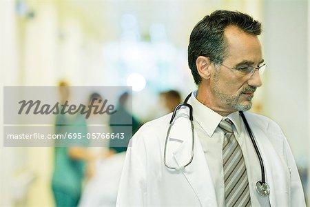 Male doctor looking away, head and shoulders, hospital corridor in background