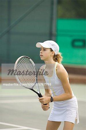 Teenage girl playing tennis, looking away