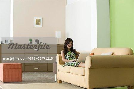 Teenage girl relaxing on sofa using laptop in living room