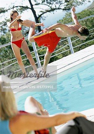 Woman Watching Teenage Girl Push Boy Into Pool Stock Photo Masterfile Premium Royalty Free Code 695 05773950