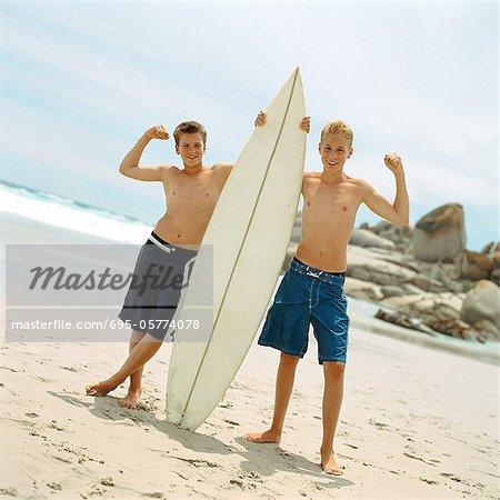 Two boys on beach holding surfboard