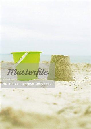 Bucket and molded sand on beach