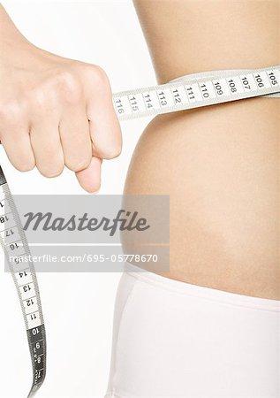 Woman squeezing measuring tape around waist