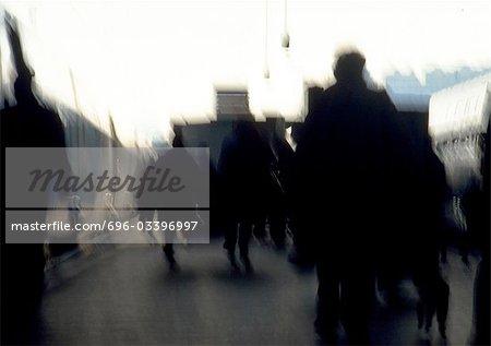 People in silhouette, walking, defocused