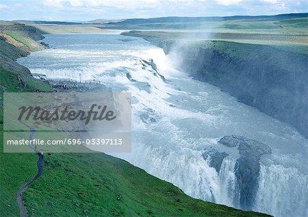 Iceland, Gullfoss waterfall, cascade and spray in green landscape