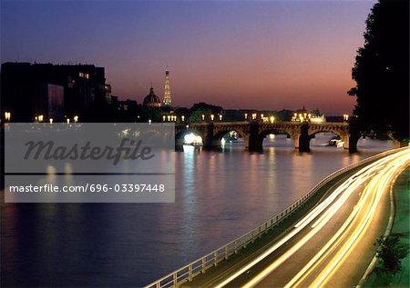 France, Paris, cars traveling on quai next to River Seine at night, blurry.