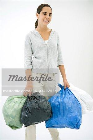 Teen girl carrying several garbage bags, smiling at camera