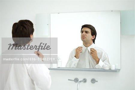 Man wearing button down shirt, adjusting collar in mirror