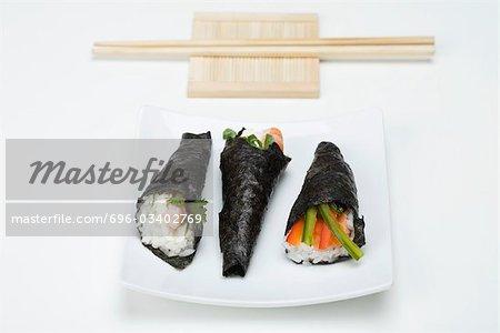 Temaki sushi on sushi plate with chopsticks