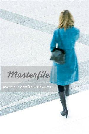Woman in blue overcoat descending steps outdoors