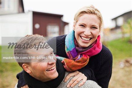 Cheerful man giving woman a piggyback ride