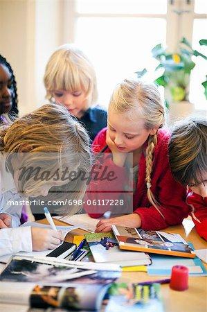 Multi ethnic children studying in classroom