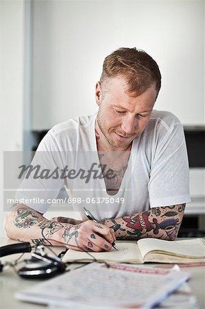 Tattooed man writing in book at desk