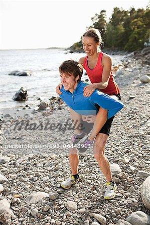 Happy man piggybacking woman at riverbank