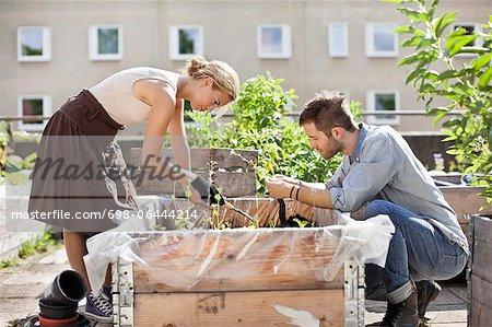 Young Caucasian couple gardening at urban garden