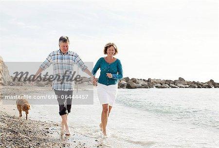 Dog chasing couple at beach