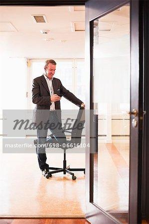 Mature businessman talking in mobile phone through headphones