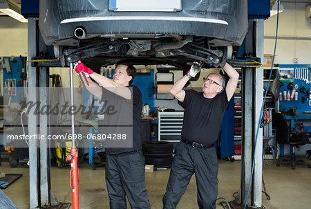 Male mechanics working underneath car at auto repair shop