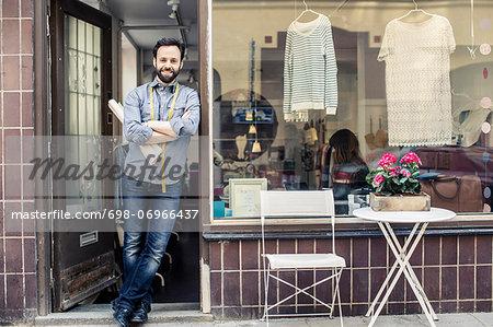 Portrait of confident mid adult male designer standing at studio entrance