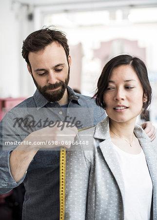 Mid adult male design professional measuring female customer's shoulder at studio