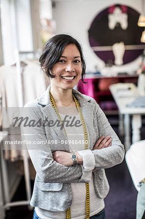 Portrait of happy female fashion designer standing arms crossed in studio