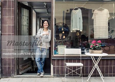 Happy female fashion designer looking away while standing at studio doorway