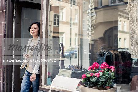 Portrait of female fashion designer holding blueprint while standing at studio entrance