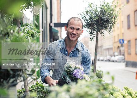 Portrait of happy male florist working outside flower shop