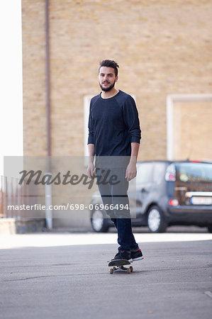 Full length portrait of young man skateboarding on street