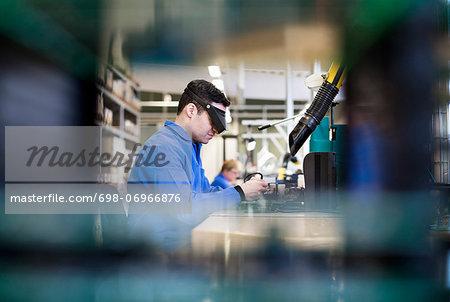 Side view of male technician wearing protective eyewear working in industry